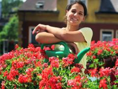 Young woman watering flowers on the balcony Stock Footage