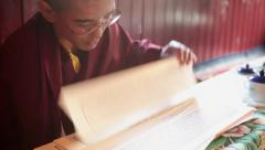A young monk reading the buddhist script during a ritual. Stock Footage
