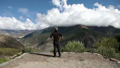 A young traveller enjoying the view atop a hill. Stock Footage