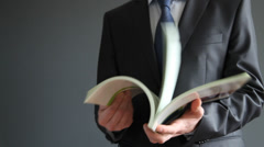 Unrecognizable businessman turning over a catalogue/book - stock footage