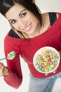 happy attractive woman eats bowl colorful breakfast cereal - stock photo