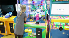 Pretty girl playing with water gun at coin-op machine Stock Footage