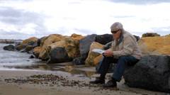 Elder man reading newspaper on the beach in the winter relaxing - stock footage