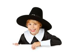 Thanksgiving: cheerful pilgrim behind white card Stock Photos