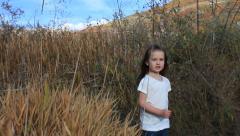 Little girl walking through tall fall grass. Stock Footage