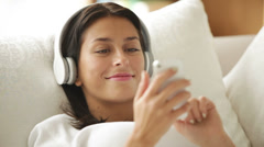 Stock Video Footage of Happy girl in headphones relaxing on sofa using cellphone looking at camera