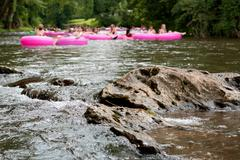 defocused people tubing down riverapproach boulder in focus - stock photo