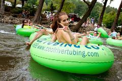 Teenage girl flashes peace sign while tubing down georgia river Stock Photos