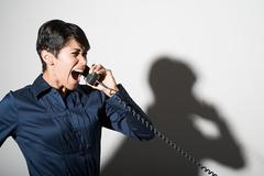 A businesswoman shouting on the telephone Stock Photos