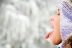 Girl in snow sticking out tongue Stock Photos