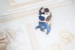 Couple hugging in their new home - stock photo