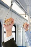 People holding handles on train - stock photo