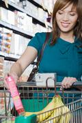 Young woman putting a packet in a shopping trolley Stock Photos