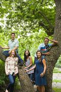 Five young friends around a tree Stock Photos