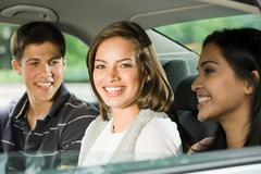 Three friends in the back of a car - stock photo