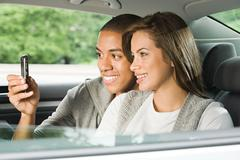 Young couple using a cellular phone in car Stock Photos