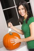 happy attractive woman cuts top off pumpkin halloween jackolantern - stock photo