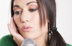 Performer female sings into microphone holding ear closed listening performan Stock Photos
