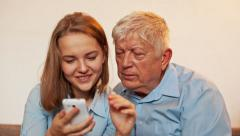 Young Girl and Old Person Learn Smartphone - stock footage