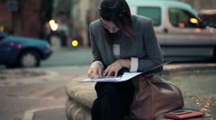 Sad, overwhelmed businesswoman with documents in the city HD - stock footage