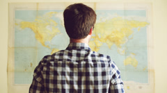 Young tourist man looking at world map Stock Footage