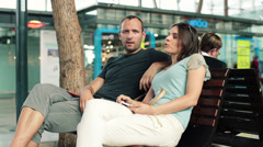 Young couple talking and relaxing on bench in shopping mal HD Stock Footage