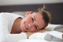 Pretty smiling woman resting on her bed Stock Photos