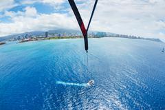 parasailing over ocean in hawaii - stock photo