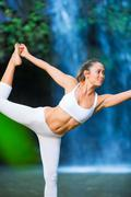 woman practacing yoga in front of beautiful waterfall - stock photo