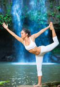Woman practacing yoga in front of beautiful waterfall Stock Photos