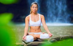Beautiful young woman in lotus position Stock Photos
