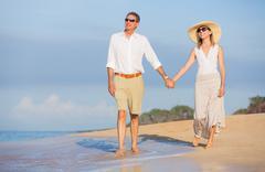middle aged couple enjoying walk on the beach - stock photo