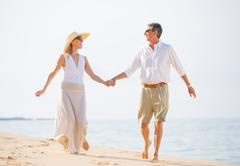 middle aged couple enjoying walk on the beach - stock photo
