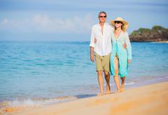 Middle aged couple enjoying walk on the beach Stock Photos