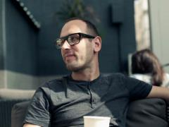 Young happy man drinking coffee and relaxing in cafe NTSC - stock footage