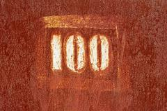 number 100 painted on an old rusty surface - stock photo