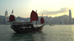 Junk ship in front of Hong Kong skyline during sunset Stock Footage