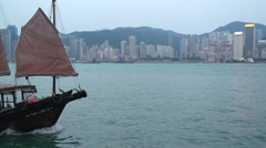 Junk ship in front of Hong Kong skyline close up Stock Footage