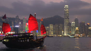 Stock Video Footage of Junk ship and cruiseship in front of Hong Kong skyline at night