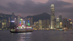 Cruiseship in front of Hong Kong skyline at night Stock Footage