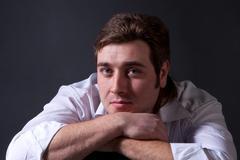 Man posing in white shirt on dark background Stock Photos