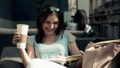 Woman laughing while reading book with funny story in cafe HD Stock Footage