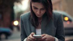 Elegant beautiful woman texting on smartphone in the city HD Stock Footage
