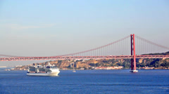 Big ship floats under the bridge on April 25 in Lisbon, Portugal Stock Footage