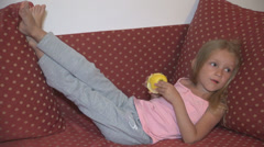 Girl Eating Apple Fruit on Sofa, Child Taking Snack, Breakfast while Watching TV Stock Footage