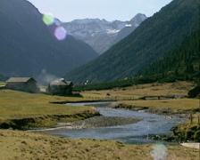 Krimmler Ache river runs gently through flat Alpine pastures - wide shot Stock Footage