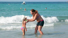 Mother playing with child on sandy beach shallow Stock Footage