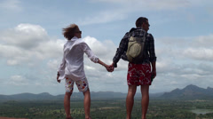 Young couple of tourists stands in the wind on top of a mountain. Stock Footage