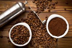 coffee beans with ground coffee and grinder - stock photo