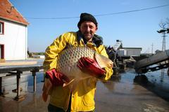 Fisherman Holding a Big Fish Stock Photos